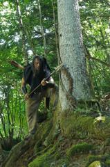 Waldläufer mit Speer und Pfeilen im Unterholz