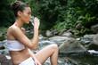 Femme buvant un verre d'eau assise au bord d'une rivière
