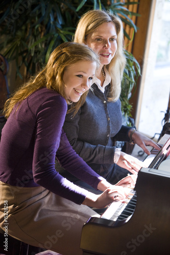 Portrait of mother and teen daughter sitting at grand piano