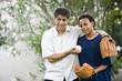 Hispanic father with African American teenage son with baseball