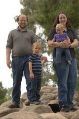 Family of 4 standing on rocks
