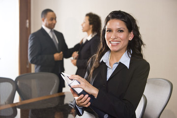 Hispanic businesswoman in boardroom, colleagues in background