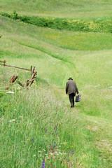 Uomo anziano che cammina solo in un prato