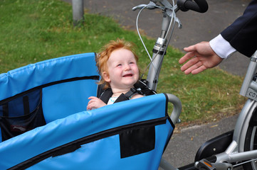Child in carrier bike says bye to daddy