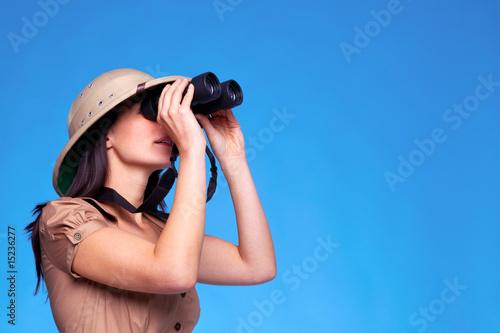 Woman in safari hat searching with binoculars