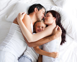 Parents and daughter relaxing on bed