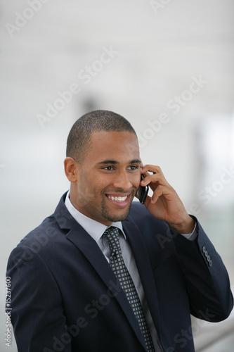 homme souriant métis en costume téléphonant
