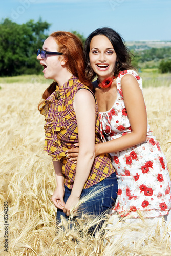 Two young girls in wheat field smiling and laughing