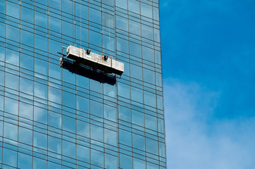 Window cleaner in a gondola cleaning the windows of a skyscraper