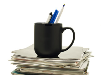 Pens in a coffee mug atop stack of magazines