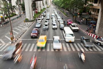 Autos, Mopeds, Taxen und Busse warten am Zebrastreifen