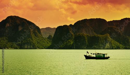 A boat sailing along the coast of Halong Bay, Vietnam.