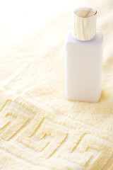 White bottle of lotion on a yellow towel
