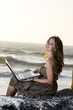 Pretty Girl working on laptop at the beach