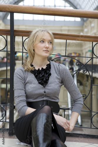 blond woman sittign on floor after shopping