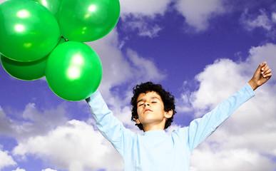 Rapaz de braços abertos com balões