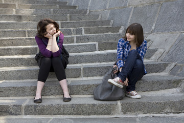 Two urban teen girls sitting on stairs