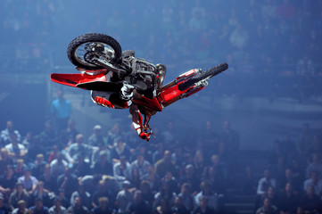 A freestyle moto cross rider performs a trick