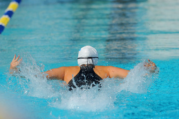 A female butterfly swimmer in action during a race.