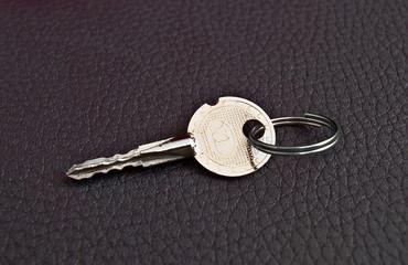 Silver key on a black  background