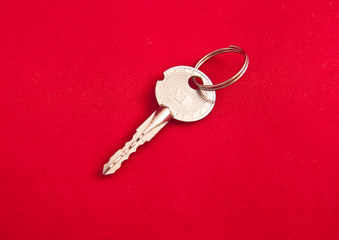 Silver key on a red background
