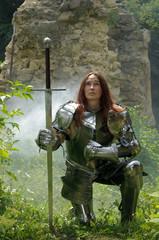 Kämpferin Jeanne D´Arc mit Schwert und Plattenrüstung knieend