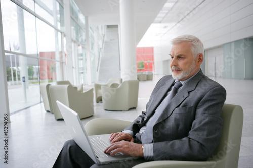 senior actif assis sur un fauteuil devant un ordinateur portable de auremar photo libre de. Black Bedroom Furniture Sets. Home Design Ideas