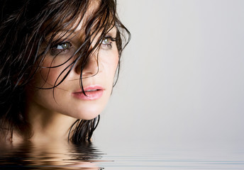 Beautiful wet brunette with reflection in water