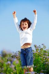 Kind in Blumenwiese jubelt