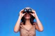 Woman in safari hat looking through binoculars