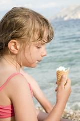 bambina con il gelato in riva al mare