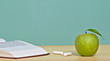 Green apple,  pieces of chalk, and open book on desk