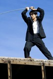 Chinese male wielding Samurai sword on train roof