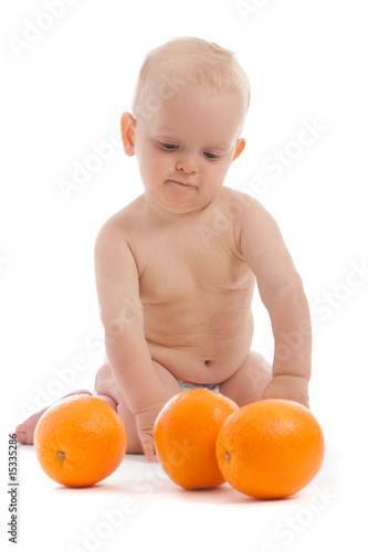 Portrait of adorable baby boy playing with three oranges