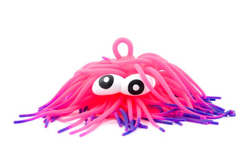 Funny pink toy like octopus on white background