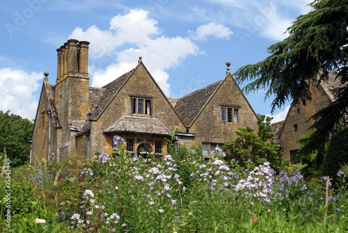 gable roof with chimney stacks. bay windows. flowers. house