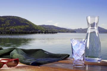 Glas Wasser mit Eiswürfel, Handtuch, Sonnenbrille und Krug am St