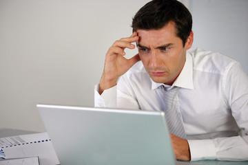 homme d'affaires réfléchissant devant un ordinateur portable