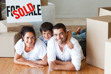 Happy family lying on the floor after buying house with boxes