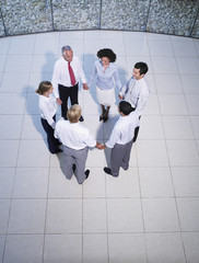 Aerial view of six office workers holding hands