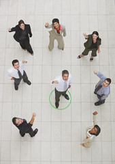 Aerial view of businessman standing in circle with businesspeople cheering