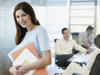 Female office worker holding papers while colleagues meet in background