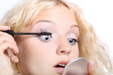 Beautiful woman applying black mascara on her eye with brush poster