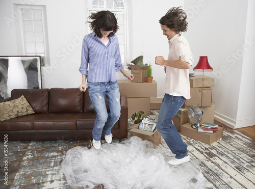 Man and woman jumping on bubble wrap in home with cardboard boxes