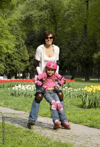 Mother with daughter ride rollerblades in the park