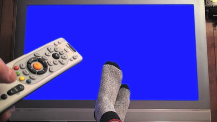 Remote control and crossed feet in front of TV - HD