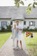 Man and woman outdoors in front of house with sold sign