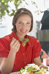 Woman eating salad outdoors