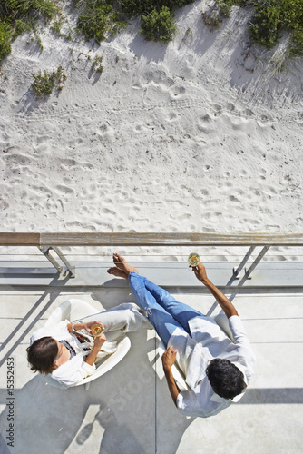Aerial view of man and woman sitting outdoors with wine and sand