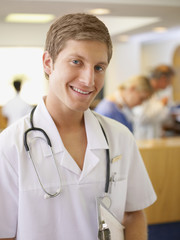 Male nurse standing with clipboard and stethoscope